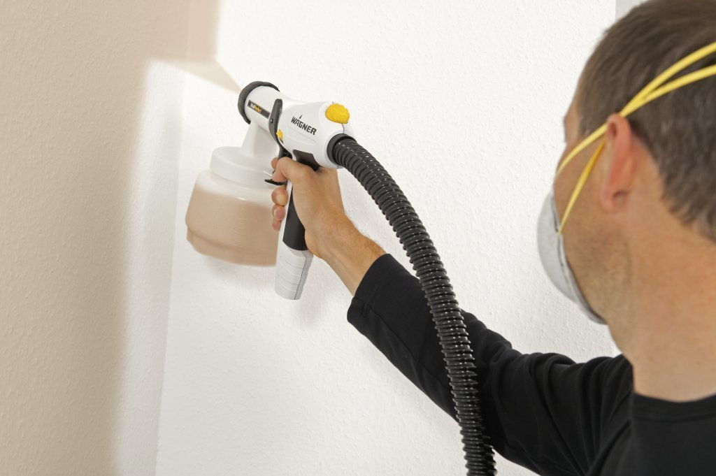 Man painting interior wall mushroom with wagner paint sprayer