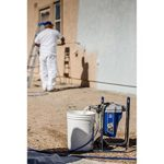 Man spraying exterior wall with paint sprayer
