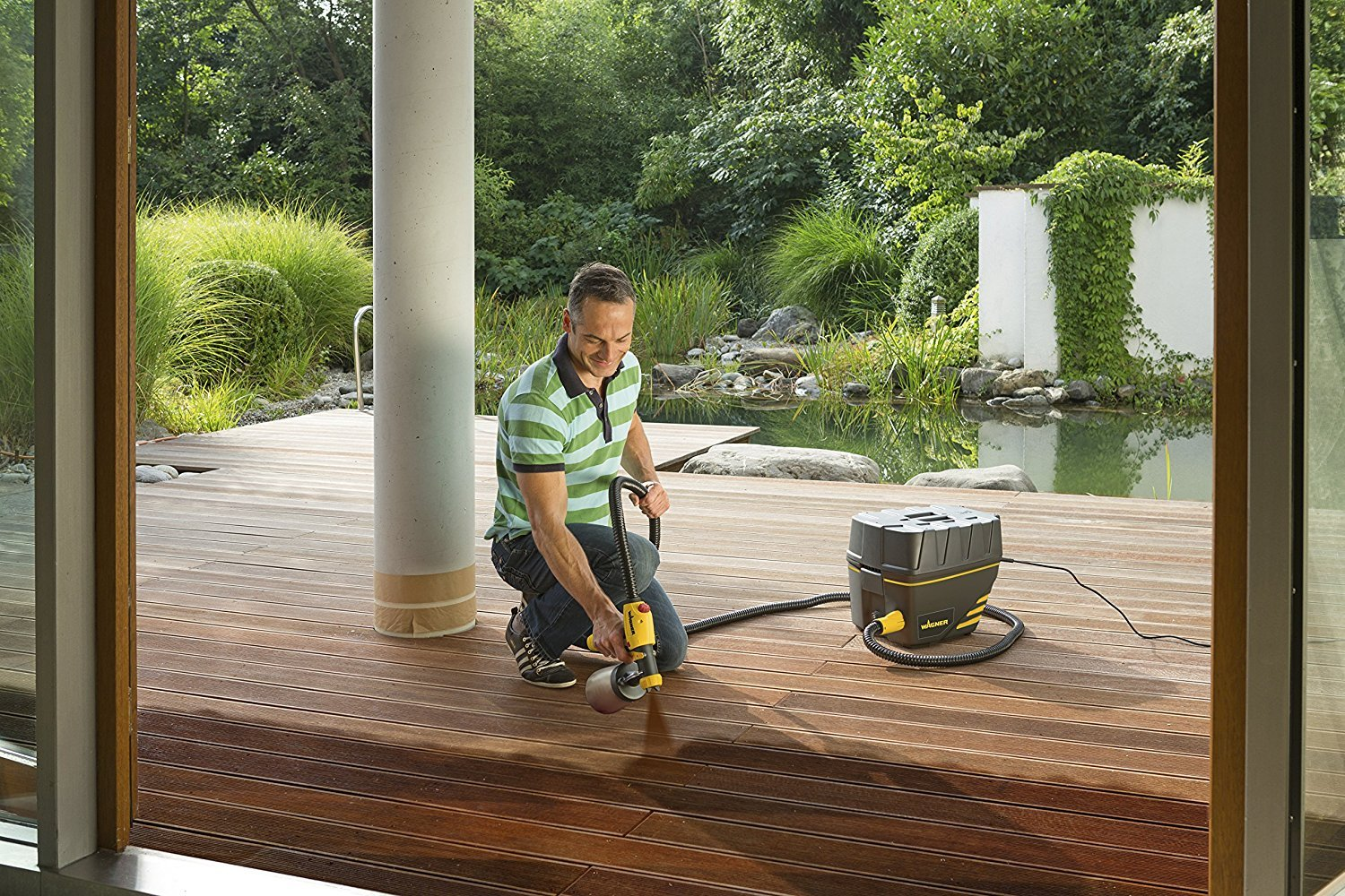 Man spraying outside deck with wagner paint sprayer