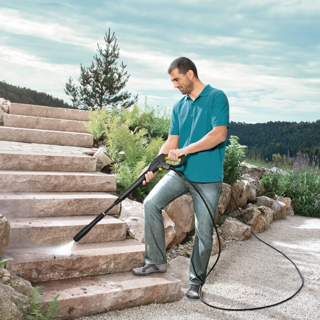 Man using karcher pressure washer on stone steps