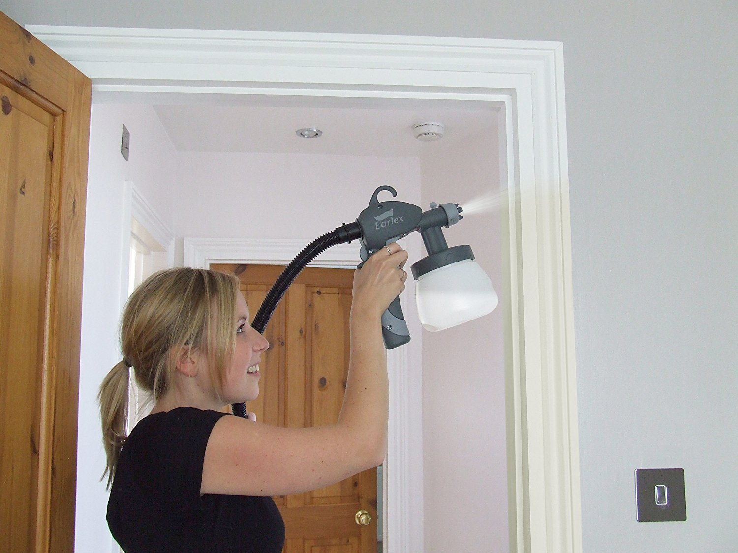 Woman painting door frame with earlex paint sprayer