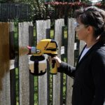 Woman painting fence with wagner paint sprayer 3