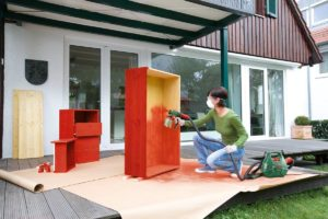 Woman painting furniture outside with bosch sprayer