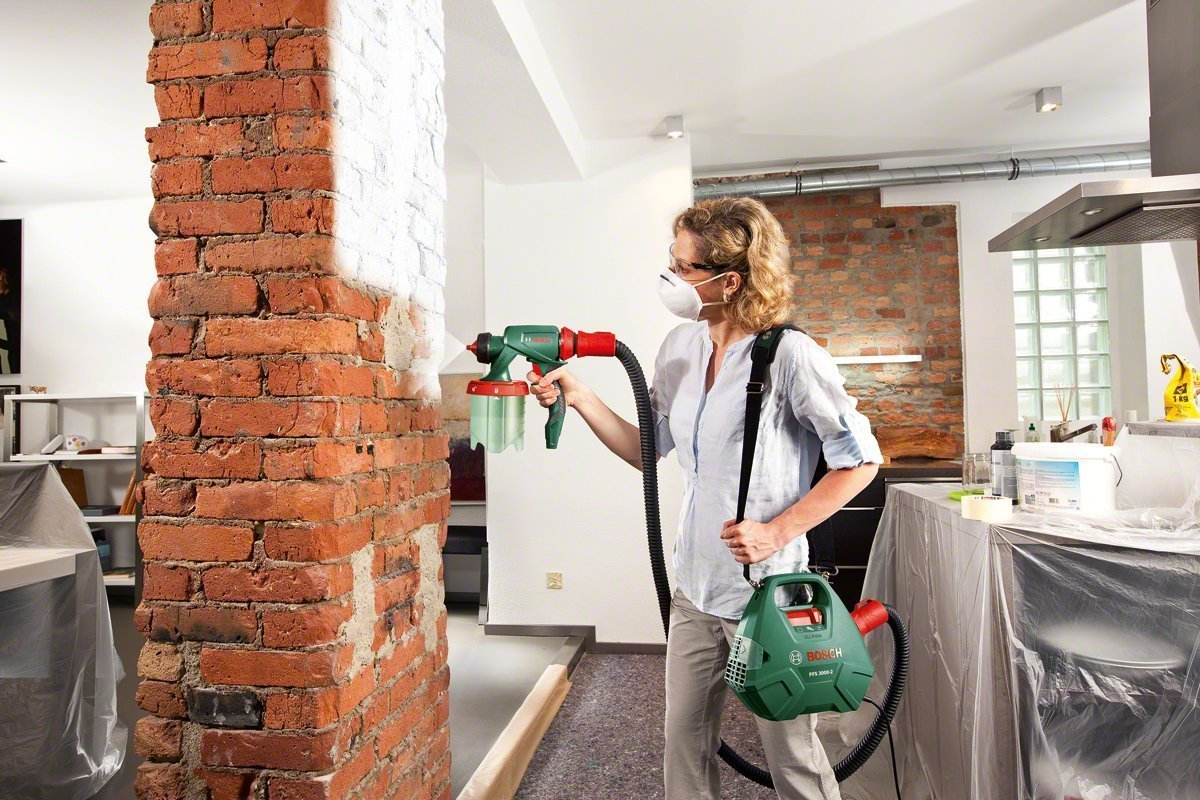 Woman painting interior brick wall