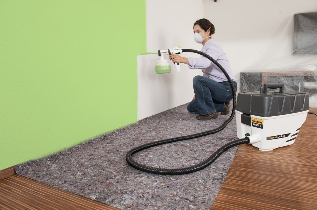 Woman painting interior wall green with wagner paint sprayer