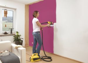 Woman painting interior wall with wagner paint sprayer