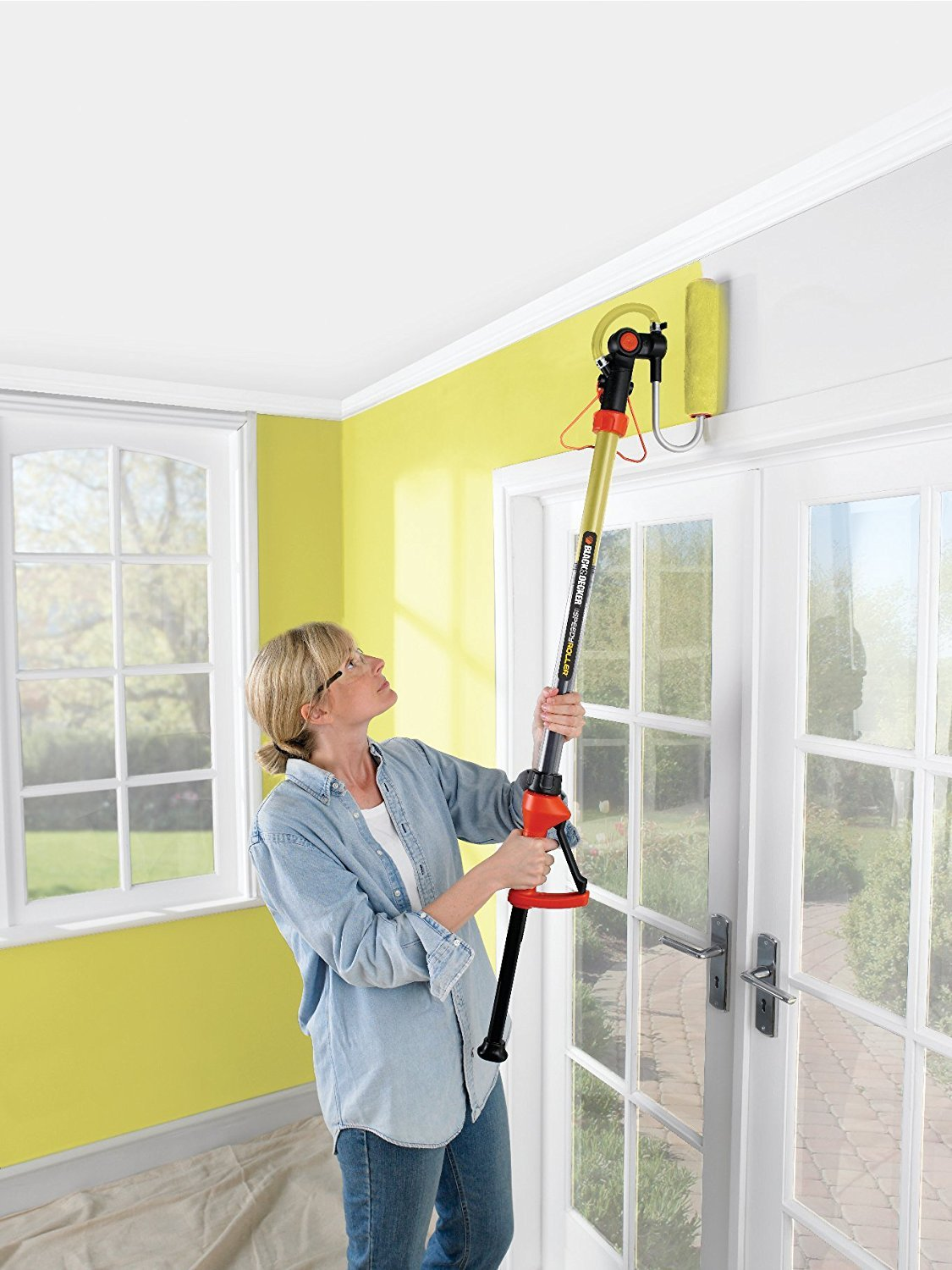 Woman painting wall yellow with black and decker roller