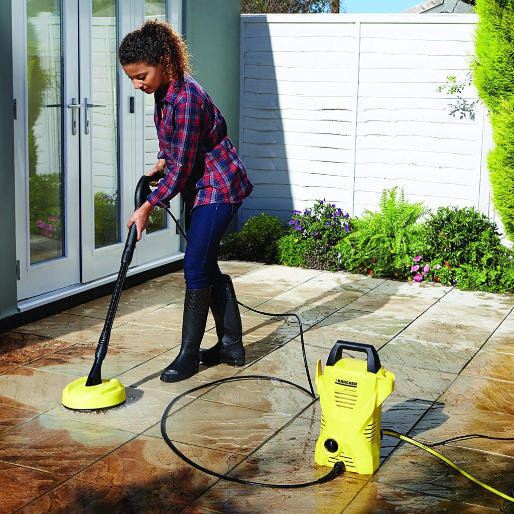 Woman using karcher pressure washer on patio